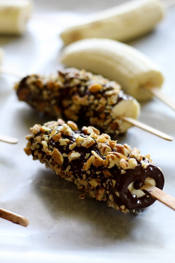 Several bananas coated in dark chocolate and topped with nuts