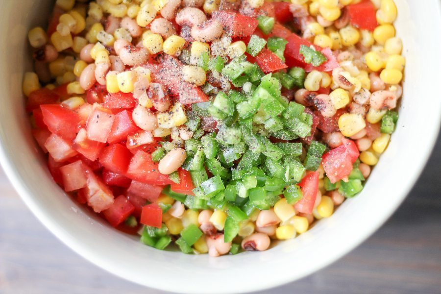 A big white bowl of black eyed pea salad with corn, jalapenos and grilled red peppers
