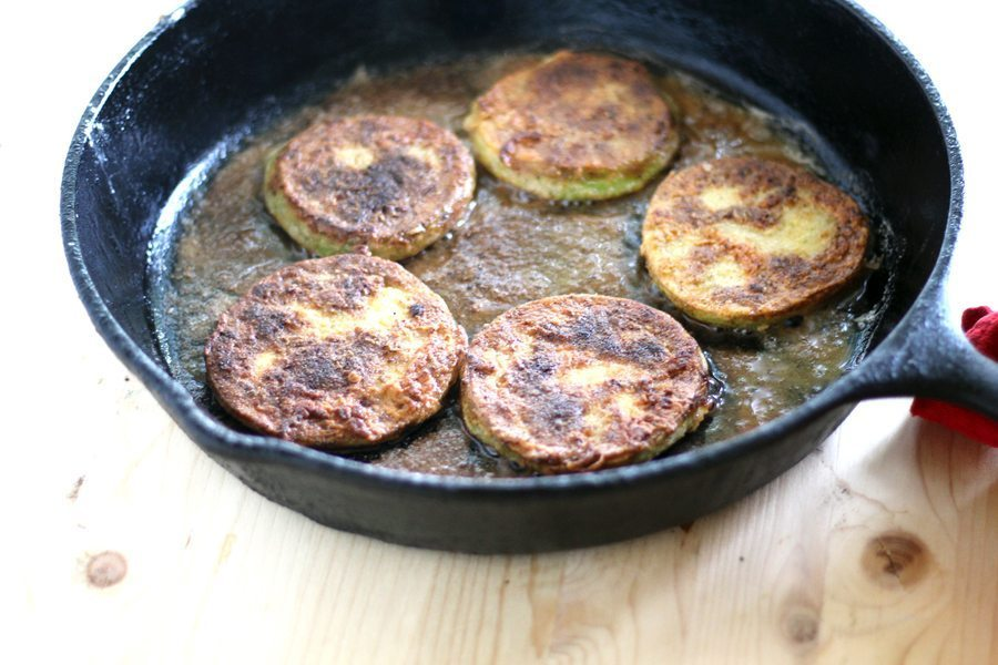 Fried green tomato slices in a cast iron skillet