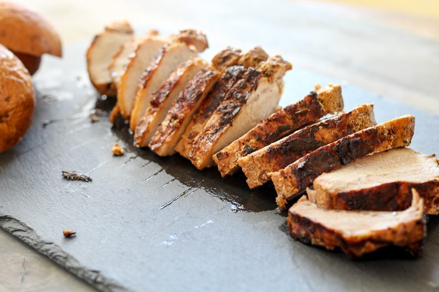 Tender and juicy grilled pork tenderloin, sliced on a slate board
