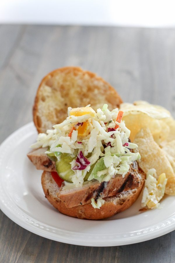 Pork tenderloin sandwich topped with fresh tangy slaw and served with potato chips