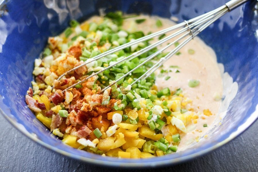 Bell pepper, jalapenos, green onions, bacon and eggs in creamy dressing in a large blue bowl
