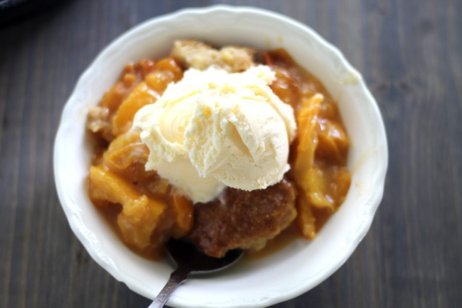 A bowl of peach cobbler with vanilla ice cream on top.