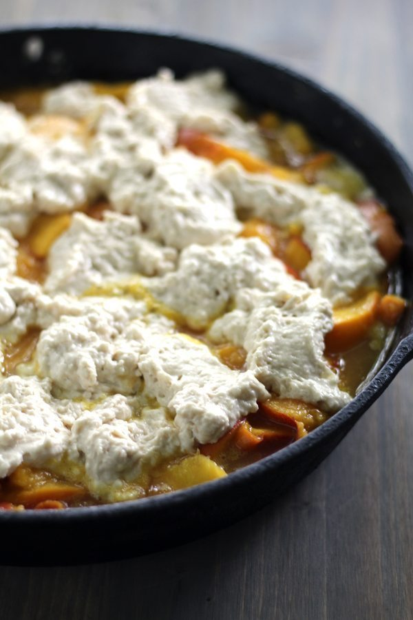 Biscuit dough on top of a skillet of peach cobbler