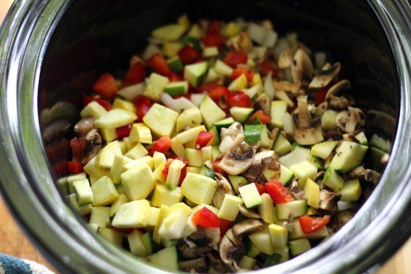A crockpot full of fresh chopped garden vegetables
