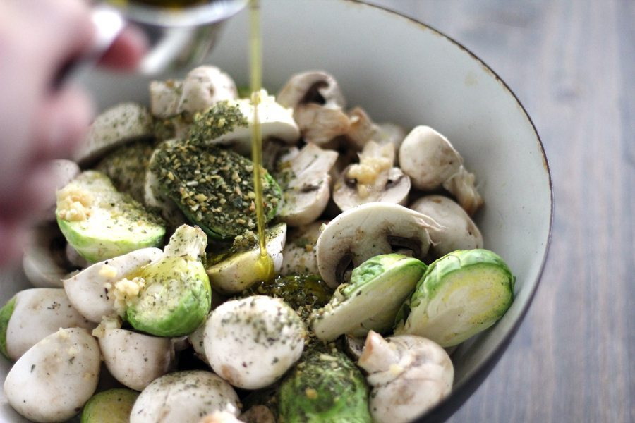 A glass bowl of fresh brussel sprouts and mushrooms topped with herbs, garlic and drizzled with olive oil