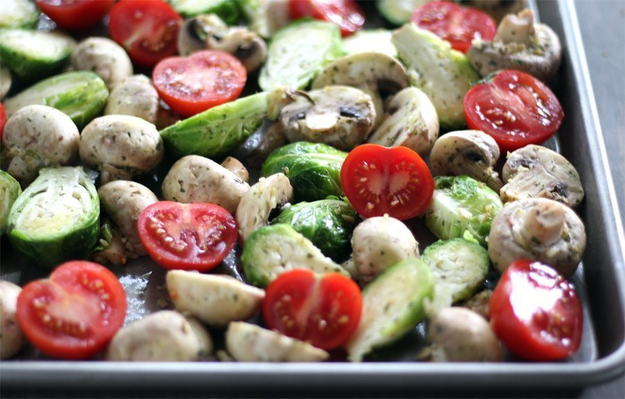 A baking sheet full of tomatoes, mushrooms and brussel sprouts