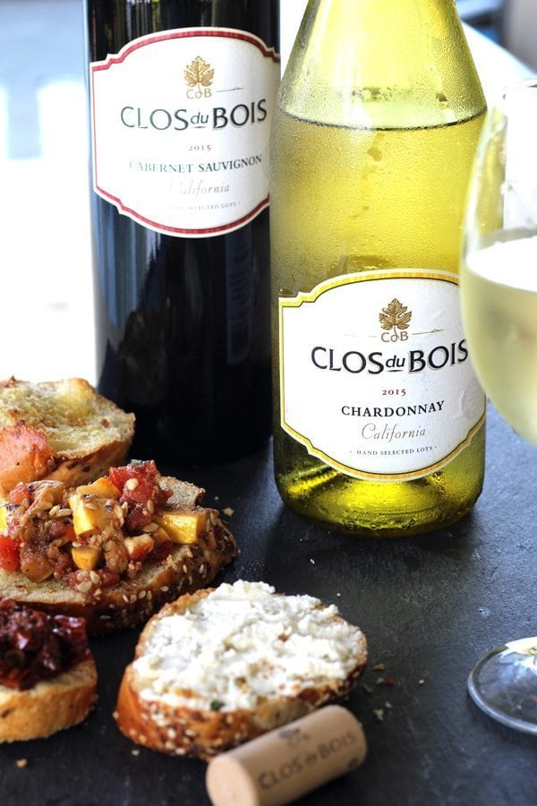 Two bottles of wine next to a chilled glass of white wine