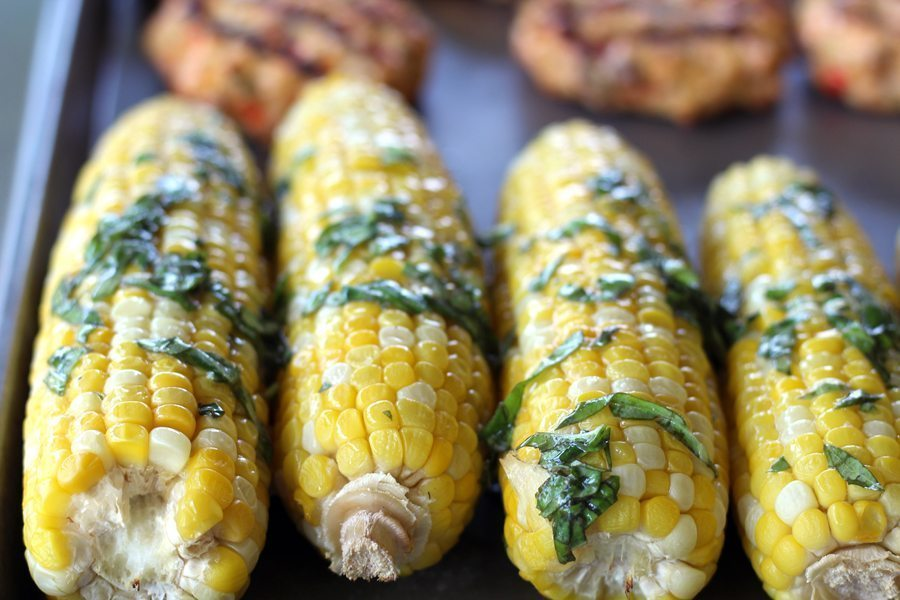 Fresh ears of corn with melted butter and wilted basil