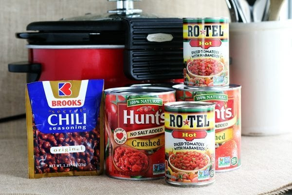 Cans of beans, tomato, Rotel in front of a Crock Pot