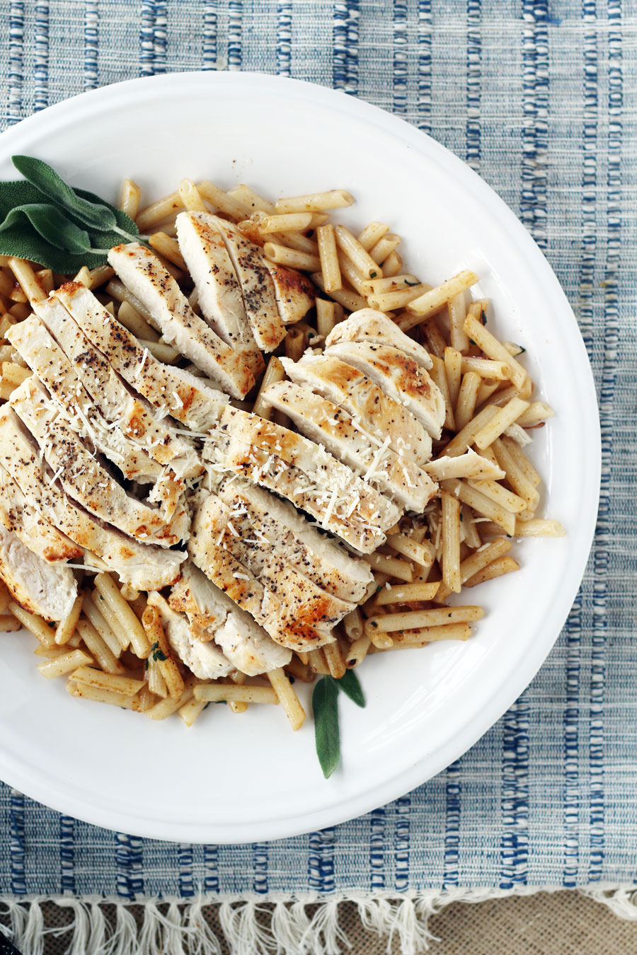 A platter of cooked and sliced chicken on a bed of penne pasta
