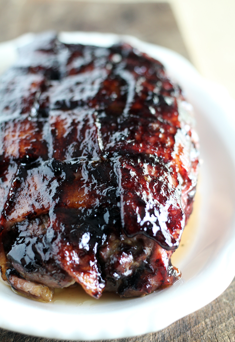 A pork tenderloin wrapped in bacon and glazed with a cherry barbecue sauce