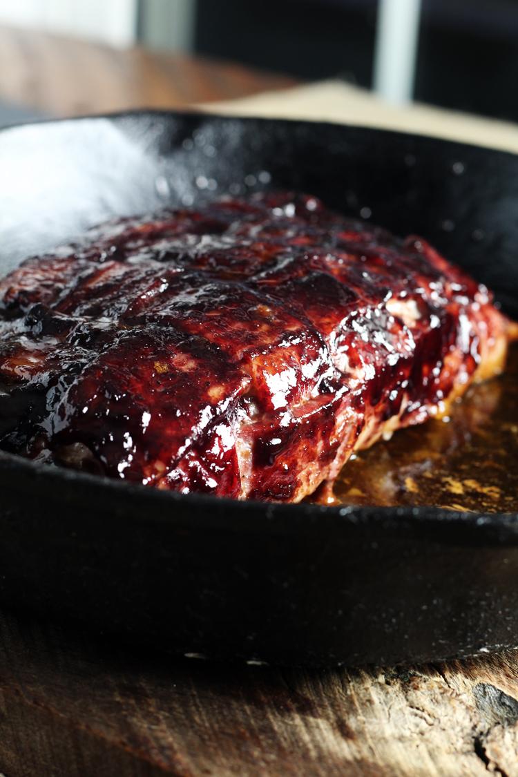 A cast iron skillet with a bacon wrapped pork tenderloin