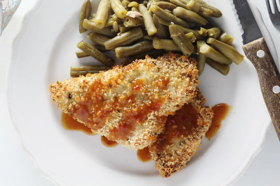 crusted turkey breast cutlets with a mustard + soy sauce on a white plate served with green beans