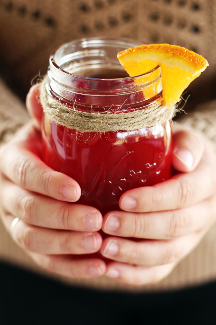 A mason jar of warm cranberry apple cider