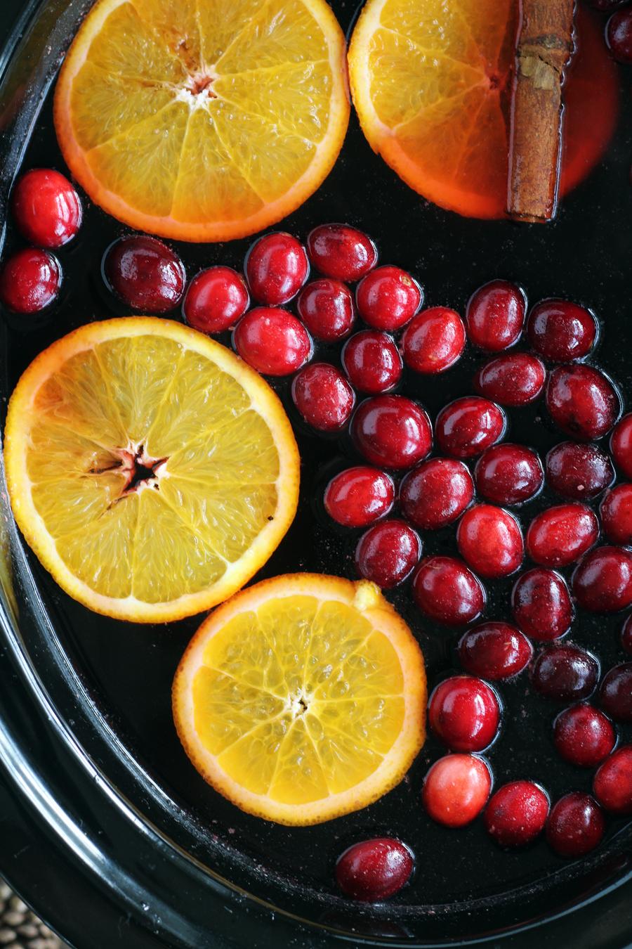 Fresh orange slices, cinnamon and cranberries floating in a crock pot of warm apple cider
