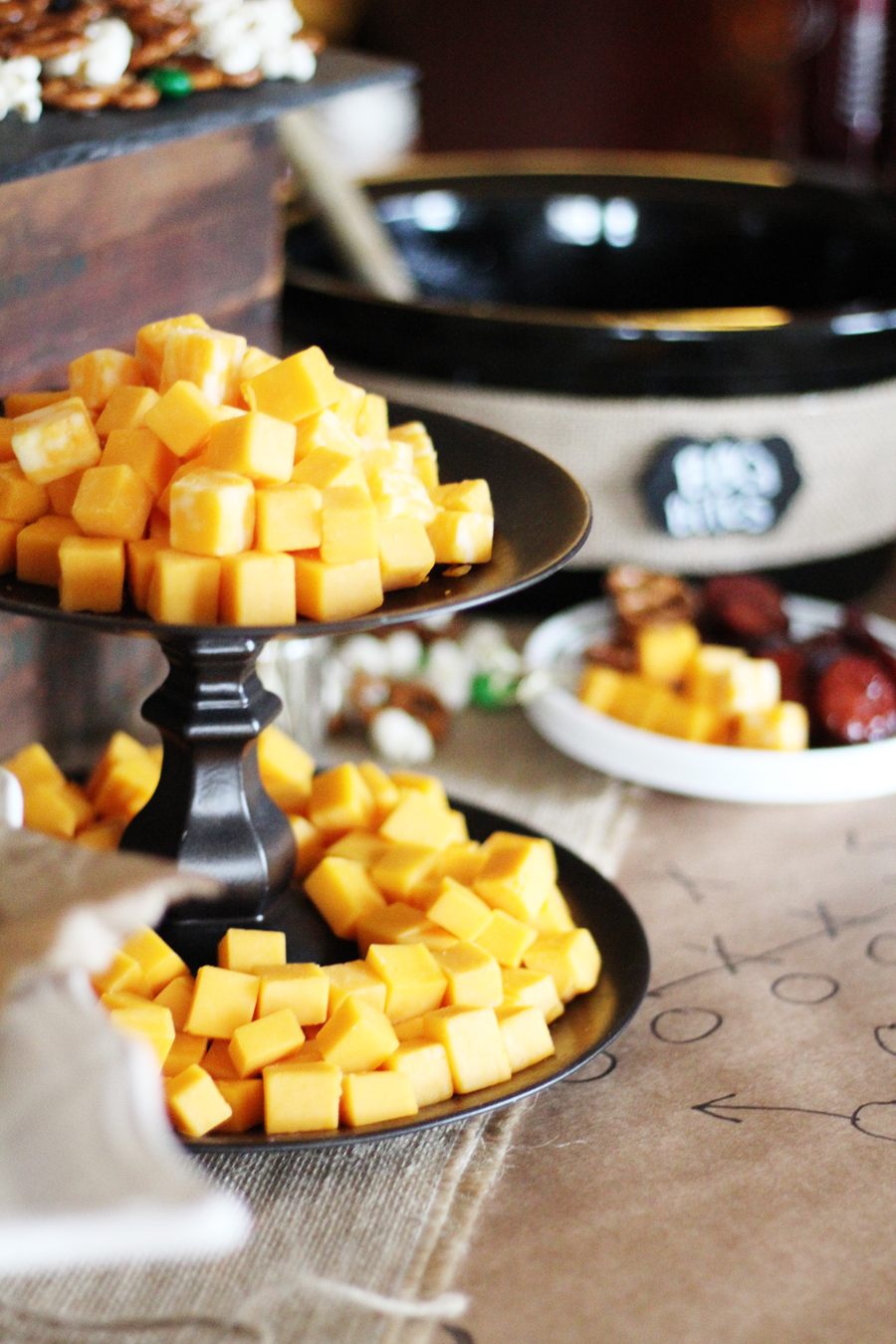 A platter of cheddar cheese cubes with a crockpot in the background