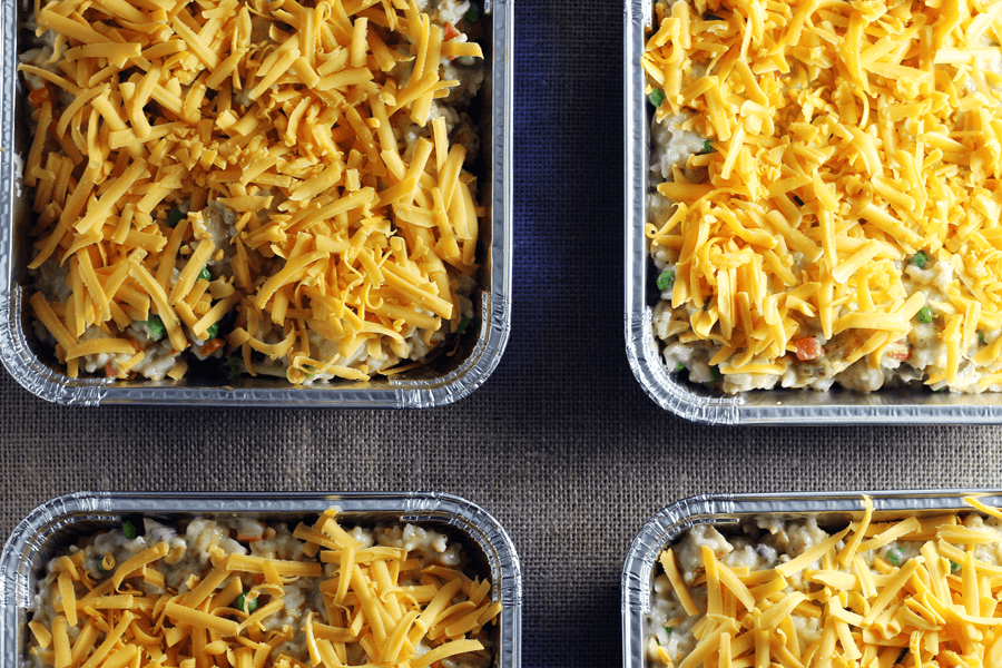 A shot of four casserole dishes with chicken rice casserole and cheesy topping