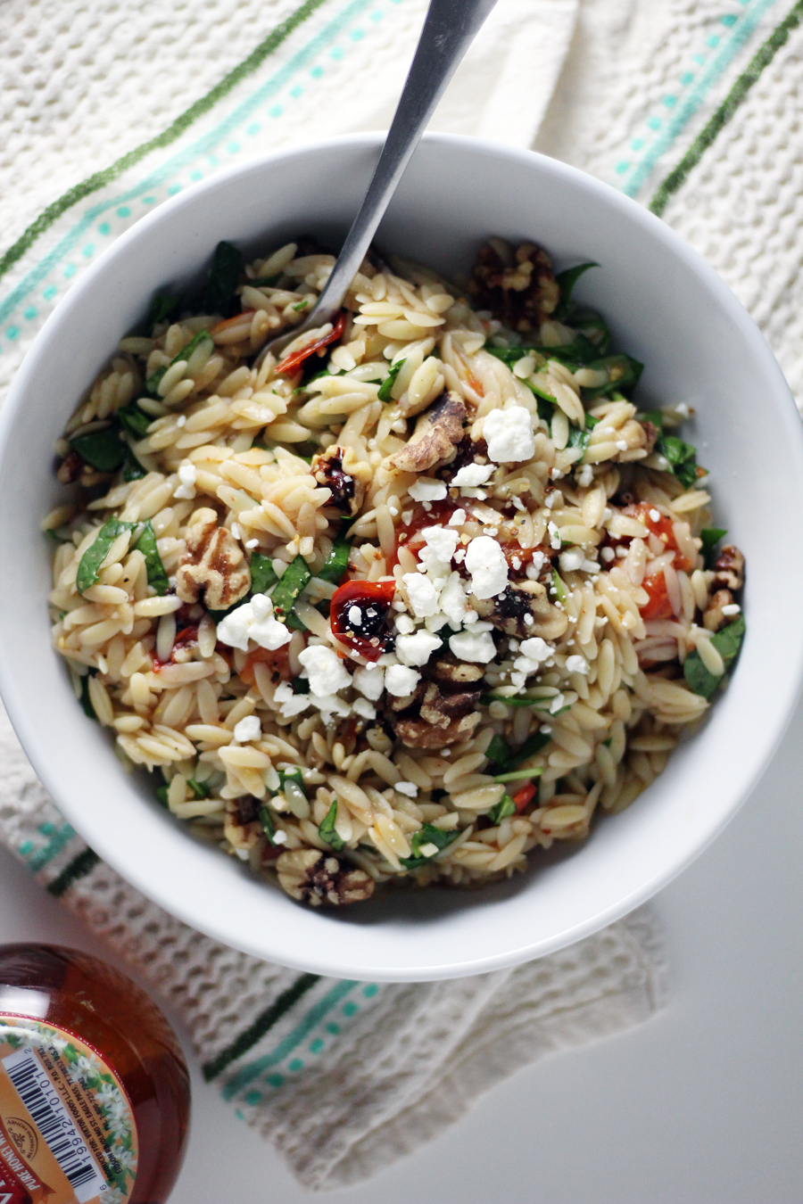Toss the honey + lemon dressing with the orzo pasta, roasted tomatoes, spinach, walnuts and sprinkle with feta.