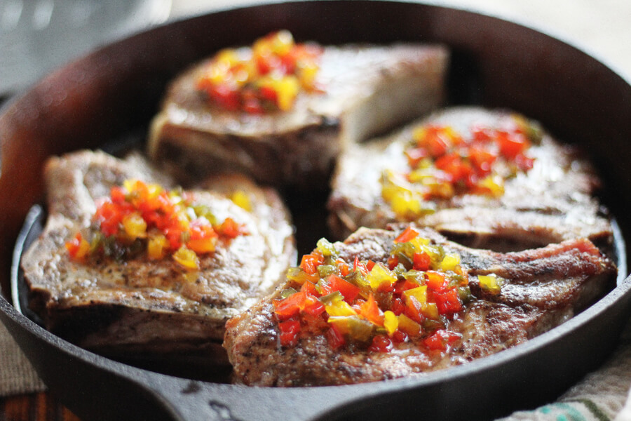 A close up shot of golden pork chops topped with an easy sweet + tangy pepper jelly insipired topping