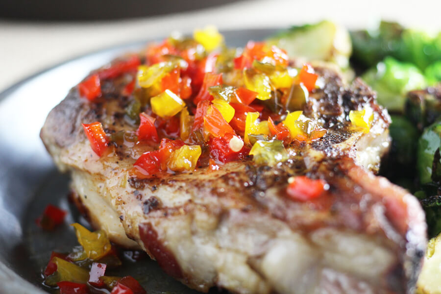 A thick cut pork chop perfectly seasoned and topped with bright peppers