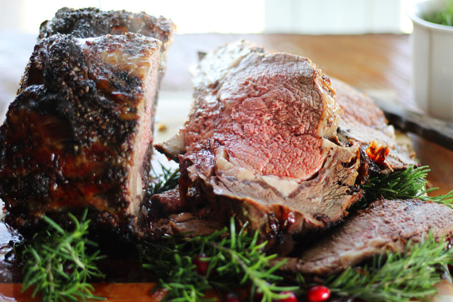 A cooked standing rib roast on a carving board, cut into thick slices with red center