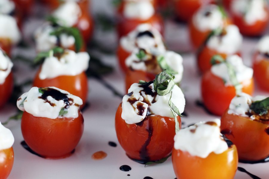 Delicious appetizer recipe for Tomato Basil Caprese Bites, served on a white platter.