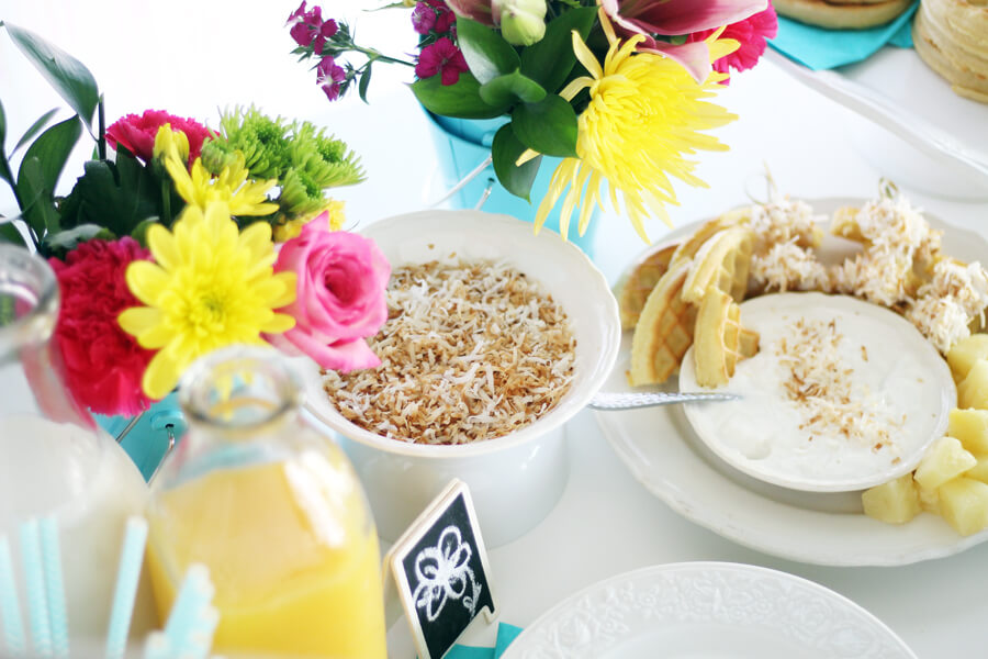 fresh flowers next to a bowl of toasted coconut, a plate of waffles and more