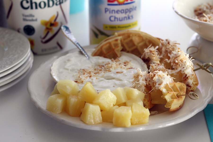 A bowl of Greek yogurt served with waffle triangles, pineapple chunks and toasted coconut