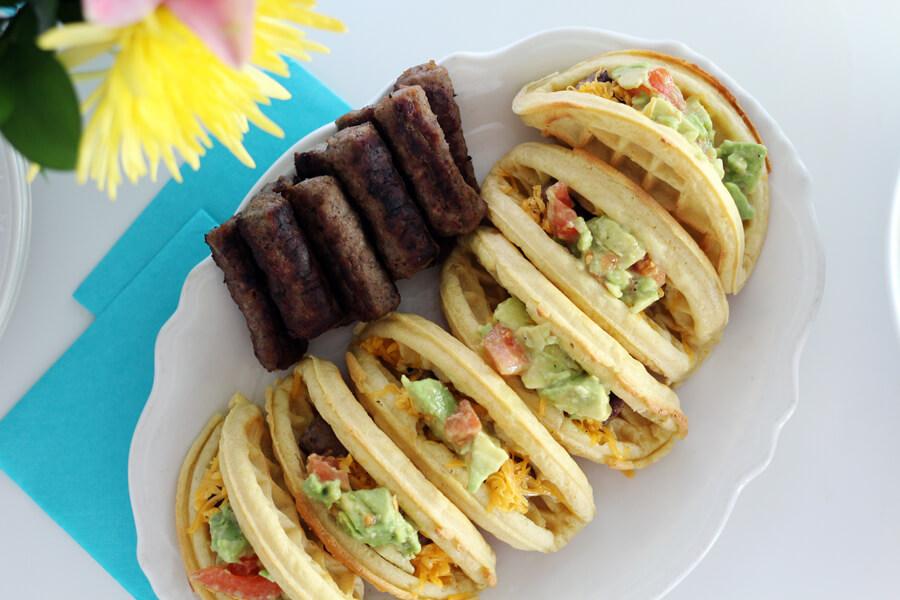 an overhead shot of savory sausage and avocado waffle tacos