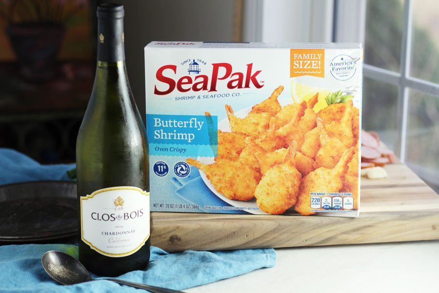 A box of SeaPak butterfly shrimp on a wooden cutting board next to a bottle of Chardonnay