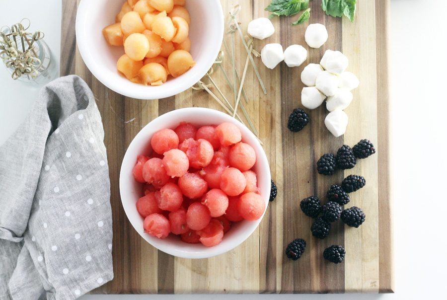 Watermelon and cantaloupe melon balls on a wooden cutting board with mozzarella and fresh blackberries