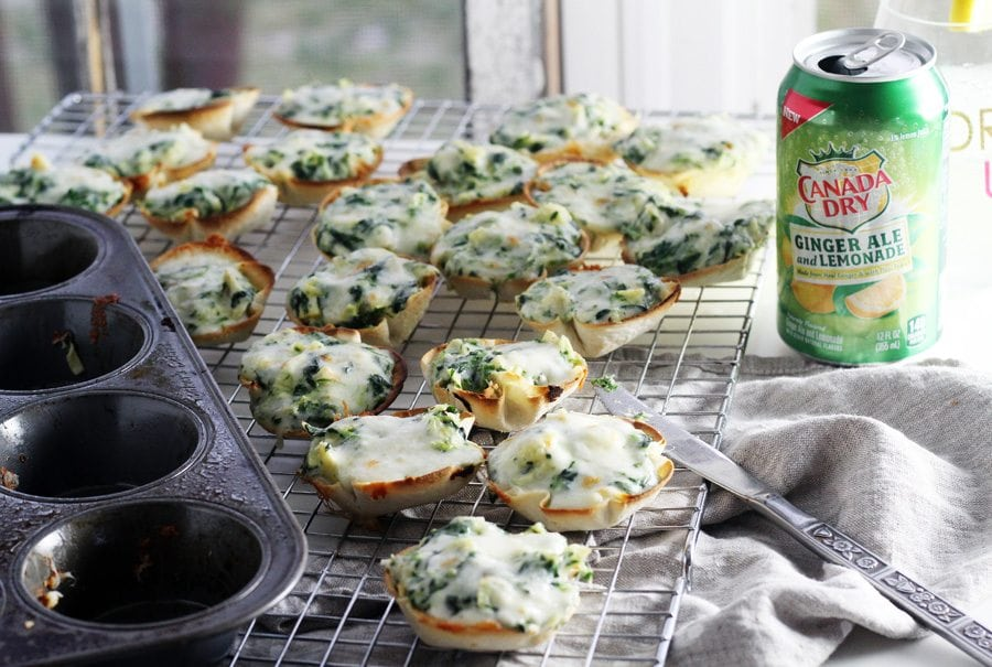 A muffin pan next to prepared spinach artichoke dip tortilla cups, next to a can of ginger ale