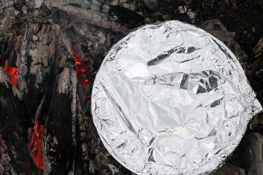 A skillet covered in foil on a campfire
