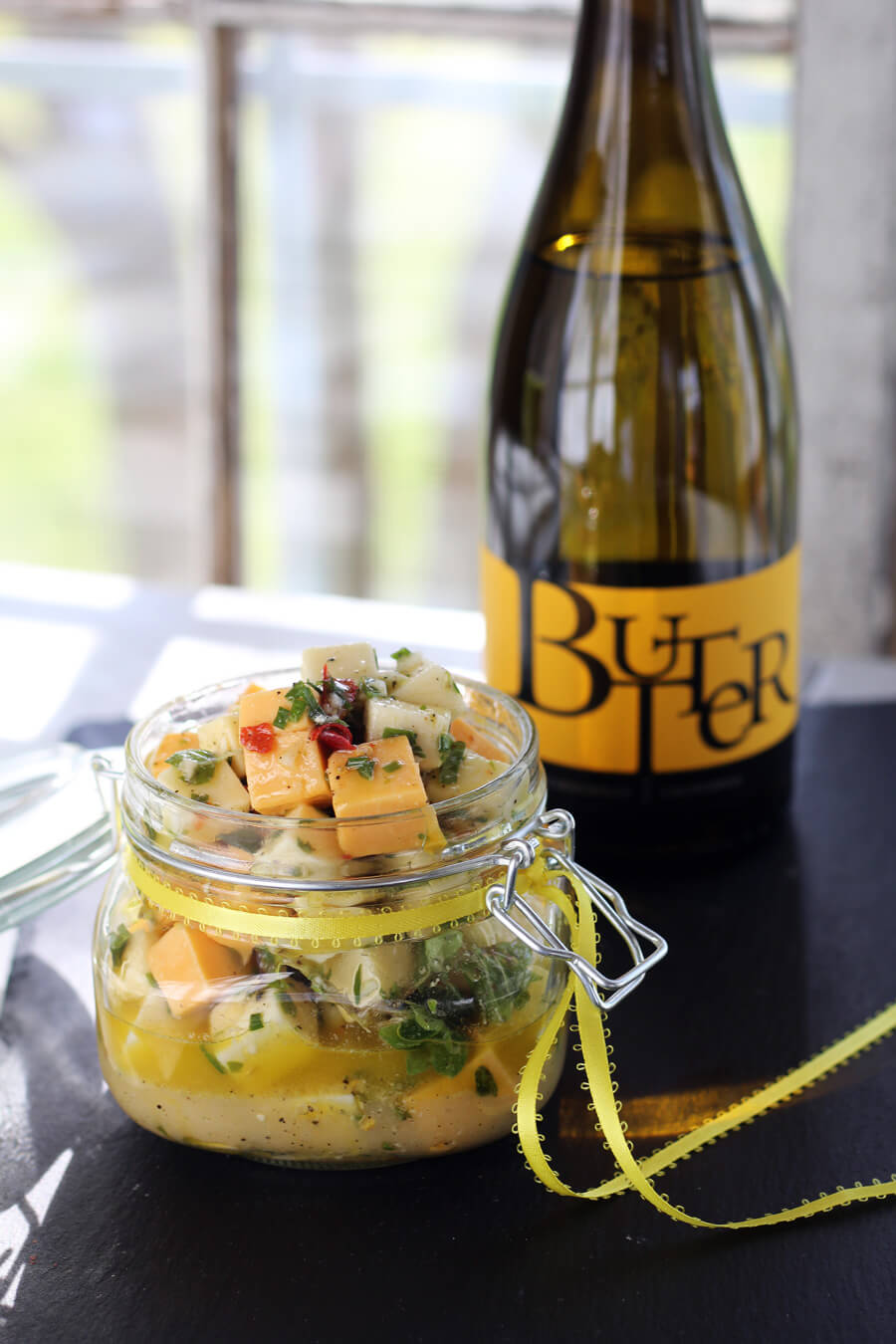A bottle of Butter Chardonnay from JaM Cellars and a gift jar of marinated cheddar cheese appetizers