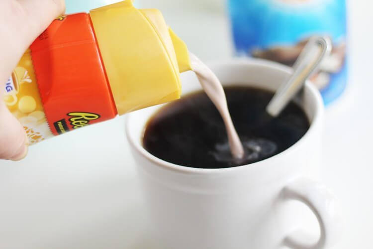 Coffee creamer being poured into a cup of coffee