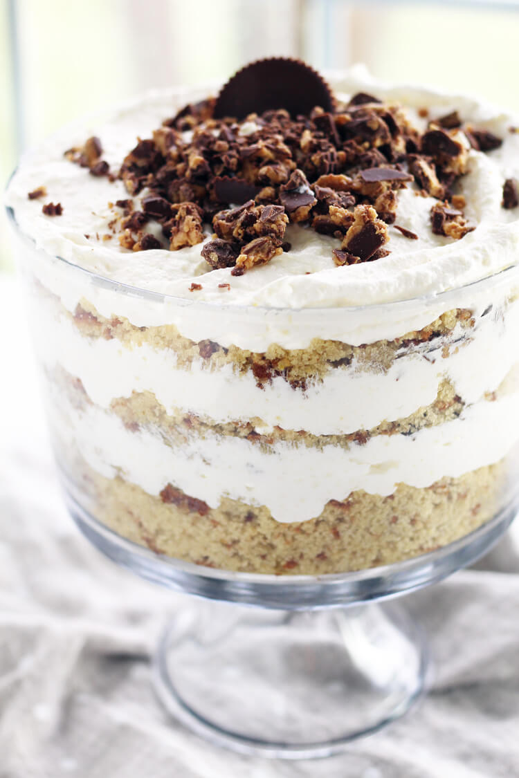 A layered punch bowl cake with crumbled peanut butter cups on top.