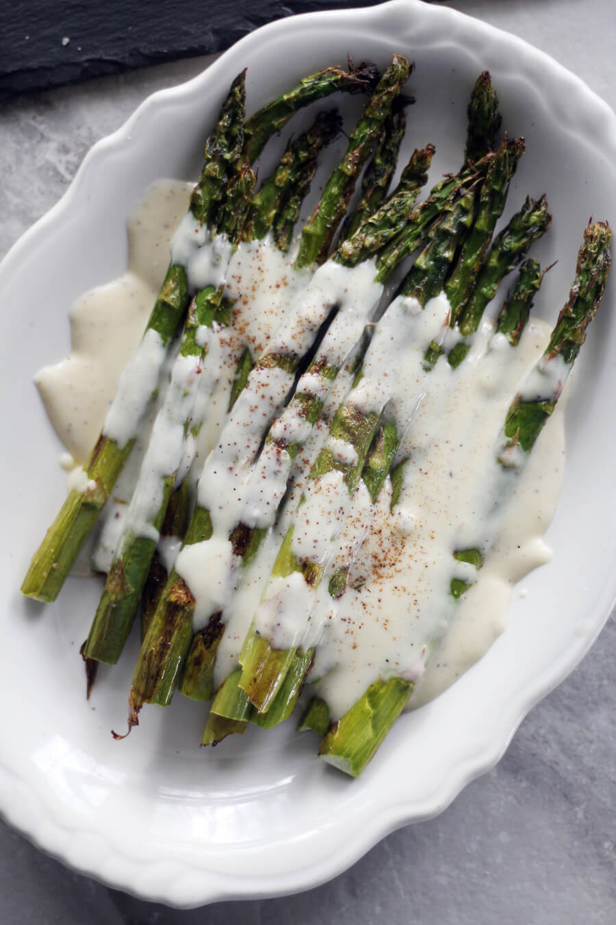 A white platter of roasted asaparagus topped with white cheese sauce and sprinkled with nutmeg