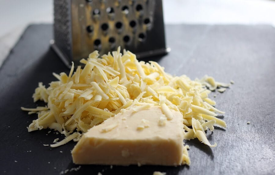 Shredded white cheddar cheese on a slate board