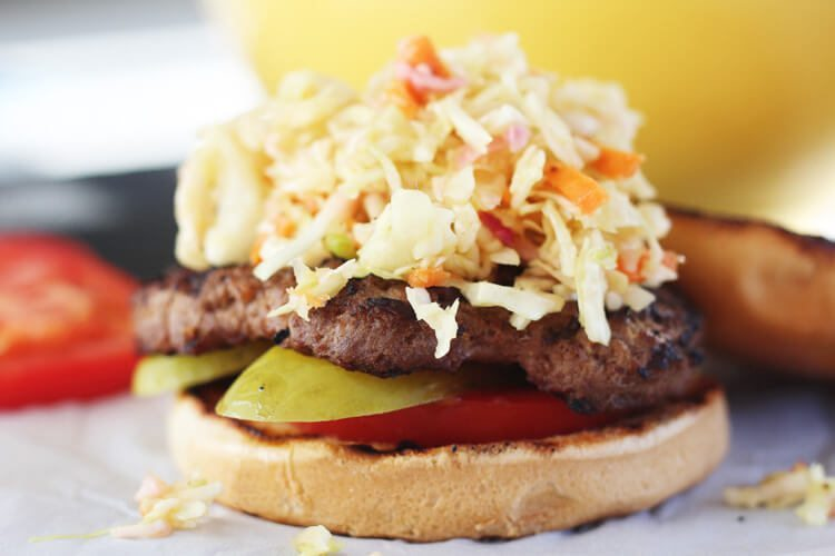 A bun with a burger pattie topped with vinegar cabbage slaw