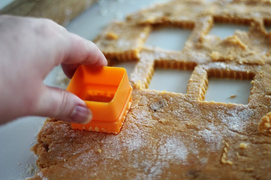 A square cookie cutter cutting out homemade dog treats
