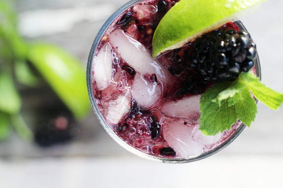 an overhead shot of a glass full of ice with lime, mint, and blackberries