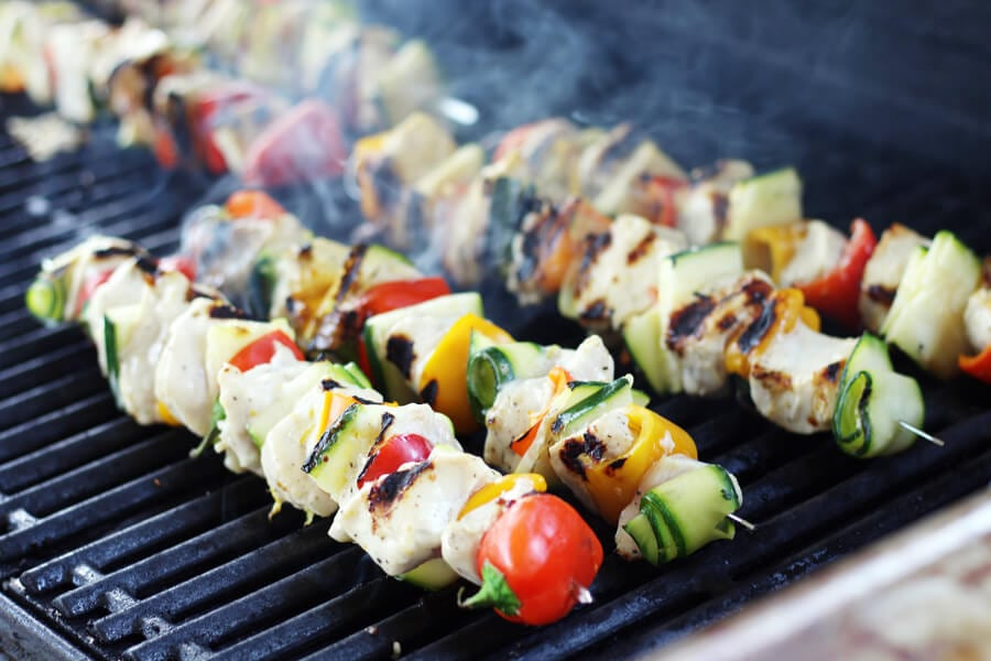 Chicken and vegetable skewers smoking on a hot grill