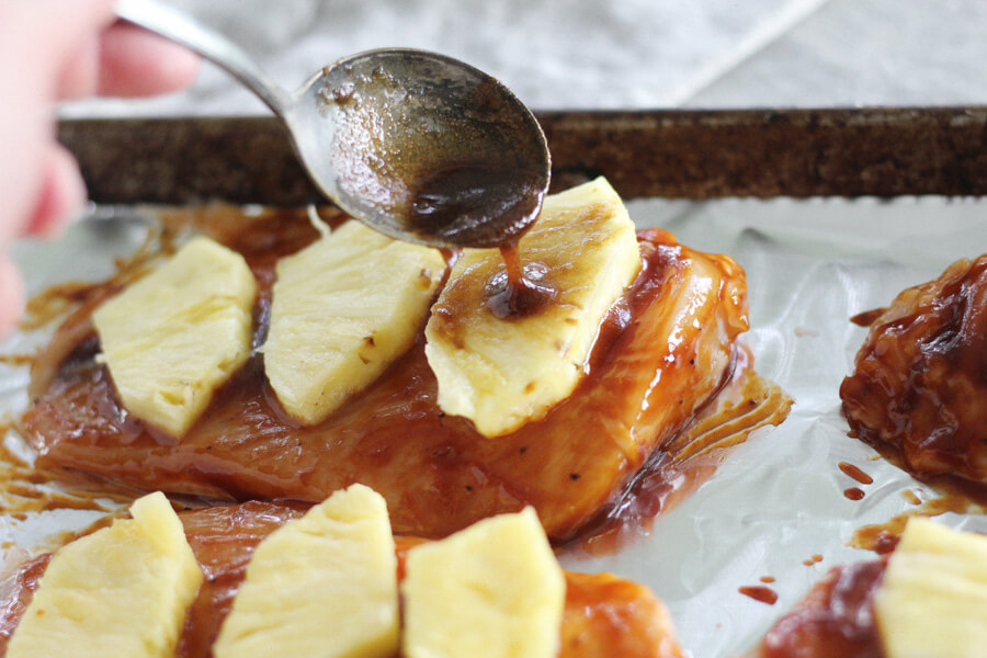 spooning brown sugar and soy sauce on top of pineapple topped chicken breasts