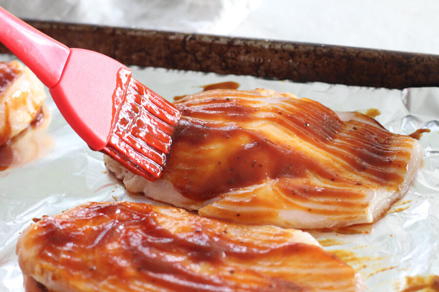 chicken breasts on a pan being brushed with barbecue sauce
