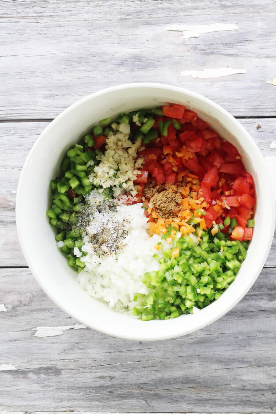 An overhead shot of a white bowl filled with salsa ingredients
