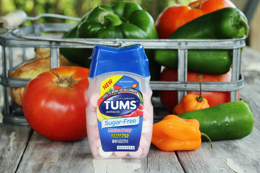 a close up shot of TUMS and fresh tomatoes, peppers and more vegetables