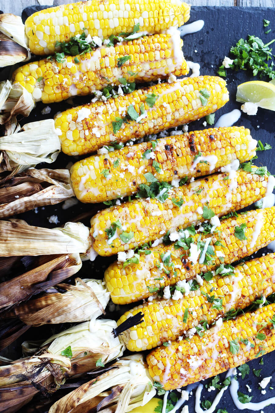 A platter of Fiesta Grilled Corn on the Cob topped with lime juice, cotija and cilantro.