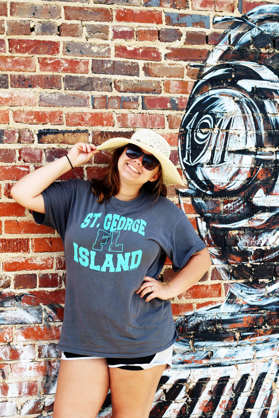 A picture of a girl wearing summer outfit in hat in sunglasses, posing in front of a brick wall with a mural painted on it