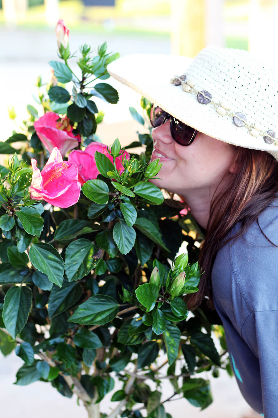 A young girl with hat and sunglasses smelling flowers